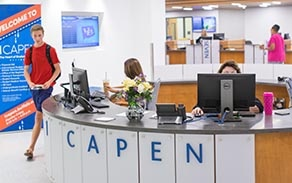 1 Capen reception desk with a student walking by on the left side.